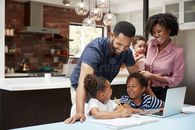 Ο πατέρας βοηθά τα παιδιά με την εργασία ενώ η μητέρα κρατά το μωρό στοκ εικόνα