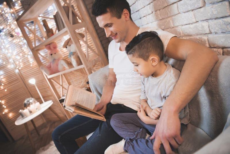 Ο πατέρας διαβάζει το βιβλίο παραμυθιών στο γιο του τη νύχτα στο σπίτι στοκ εικόνα