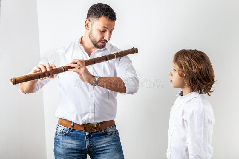 Ο πατέρας διδάσκει το γιο για να παίξει το φλάουτο μπαμπού στοκ εικόνα με δικαίωμα ελεύθερης χρήσης