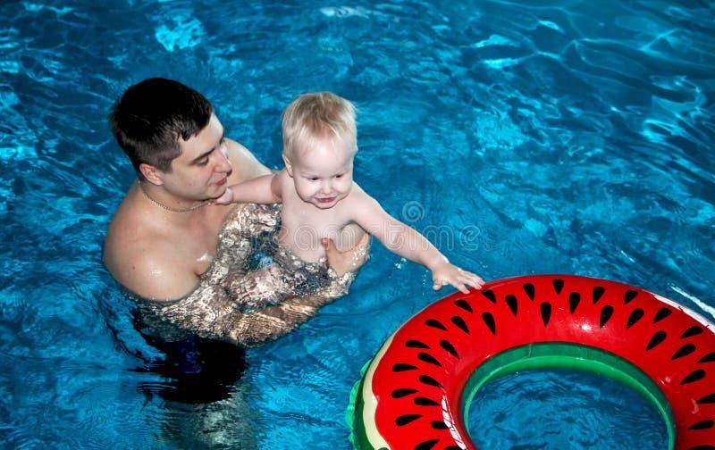 Ο πατέρας και ο γιος κολυμπούν στη λίμνη στοκ εικόνες