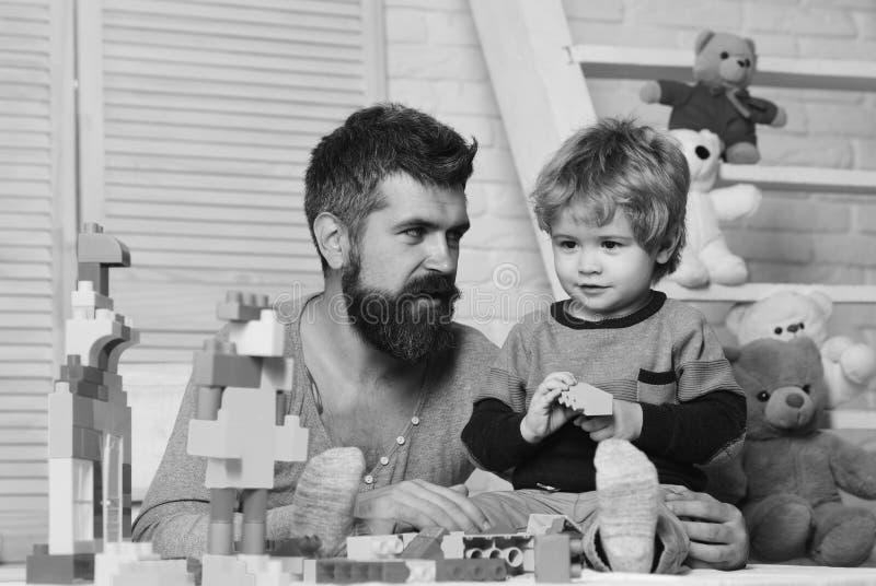 Ο πατέρας και ο γιος με τα πρόσωπα χαμόγελου δημιουργούν τις ζωηρόχρωμες κατασκευές στοκ εικόνες με δικαίωμα ελεύθερης χρήσης