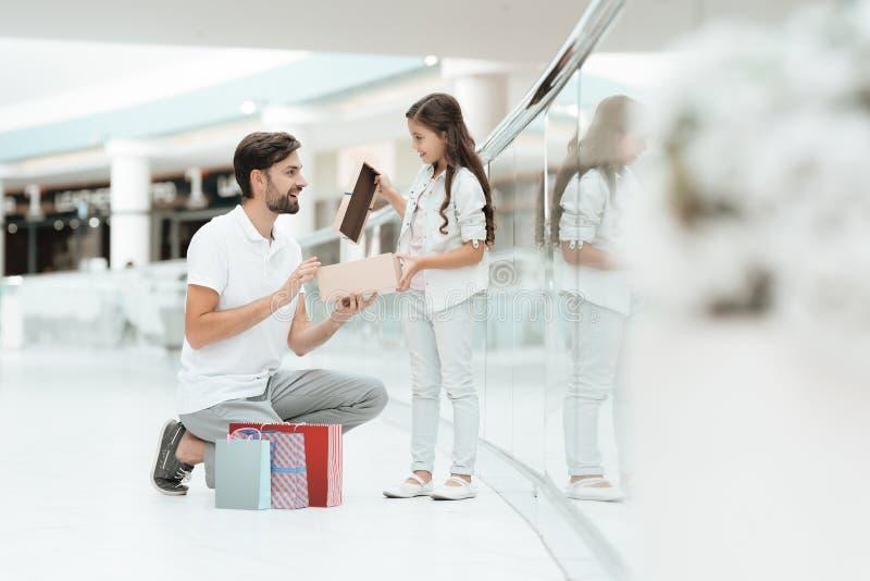 Ο πατέρας και η κόρη ανοίγουν το νέο παρόν για το κορίτσι στη λεωφόρο αγορών στοκ φωτογραφία με δικαίωμα ελεύθερης χρήσης