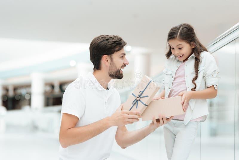 Ο πατέρας και η κόρη ανοίγουν το νέο παρόν για το κορίτσι στη λεωφόρο αγορών στοκ εικόνα