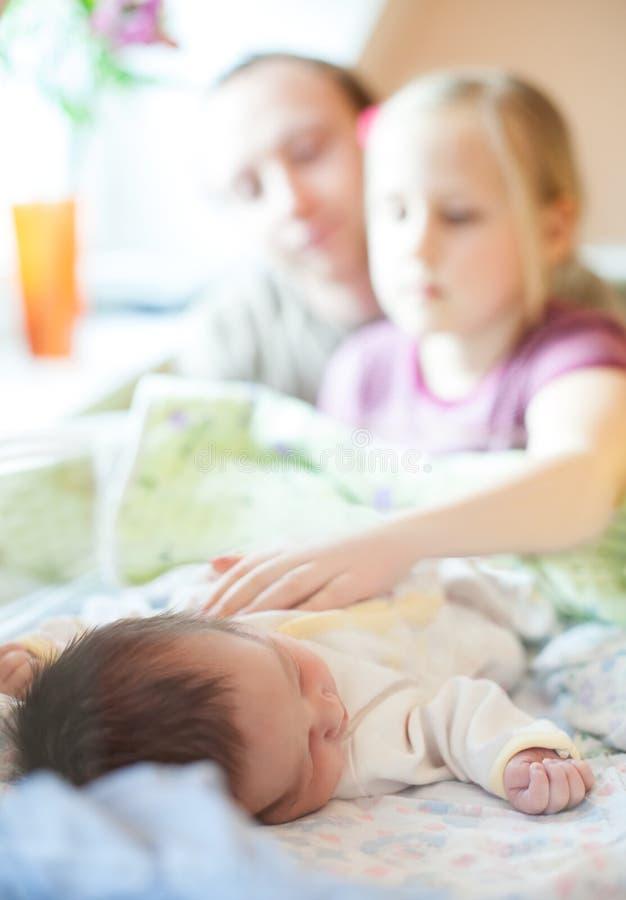 Ο πατέρας και η κόρη εξετάζουν το νεογέννητο οικογενειακή έννοια στοκ εικόνα