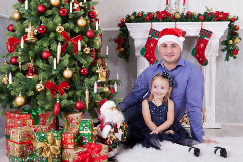 Ο πατέρας και η κόρη κάθονται κοντά στο χριστουγεννιάτικο δέντρο Ο πατέρας έχει ένα καπέλο Άγιου Βασίλη στο κεφάλι του Μια εστία  στοκ εικόνες με δικαίωμα ελεύθερης χρήσης