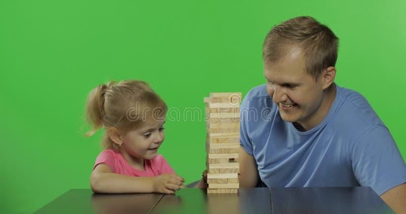 Ο πατέρας και η κόρη παίζουν το jenga Λίγο παιδί τραβά τους ξύλινους φραγμούς από τον πύργο στοκ εικόνα με δικαίωμα ελεύθερης χρήσης