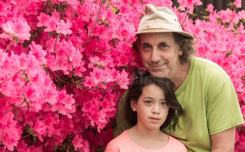 Ο πατέρας και η κόρη που στέκονται μπροστά από τη ρόδινη αζαλέα ανθίζουν στην μπλούζα την καυτή ημέρα άνοιξη στοκ εικόνα με δικαίωμα ελεύθερης χρήσης
