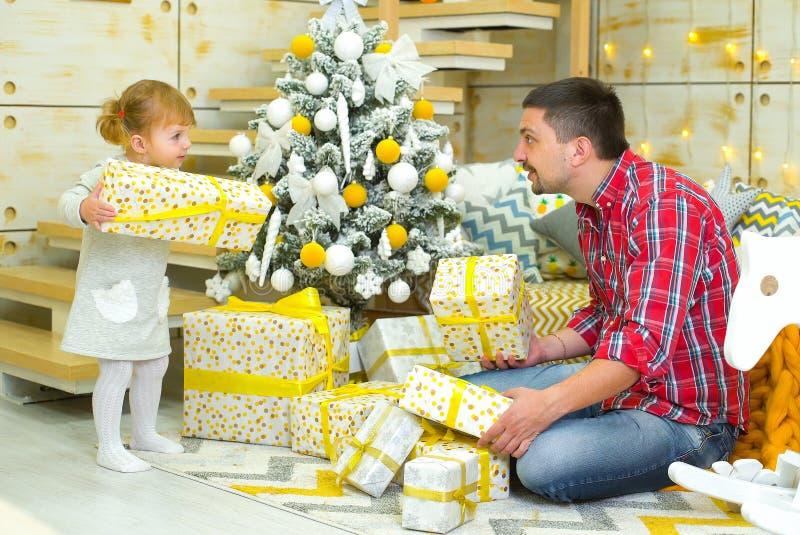 Ο πατέρας και λίγη κόρη με τα κιβώτια δώρων διακόσμησαν πλησίον το χριστουγεννιάτικο δέντρο στο σπίτι στοκ εικόνα