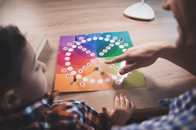 Ο πατέρας και λίγος γιος παίζουν το επιτραπέζιο παιχνίδι τη νύχτα στο σπίτι στοκ φωτογραφίες