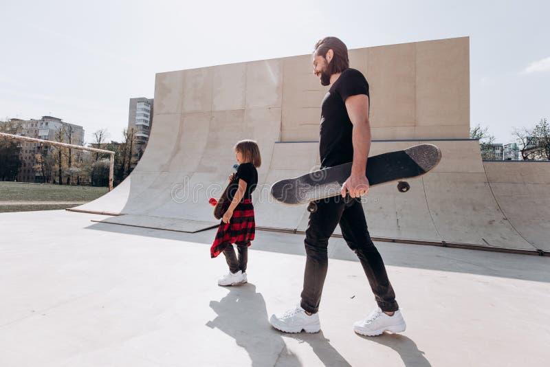 Ο πατέρας και ο μικρός γιος του που ντύνονται στο μοντέρνο περίπατο περιστασιακών ενδυμάτων με skateboards στο τους παραδίδουν έν στοκ εικόνα