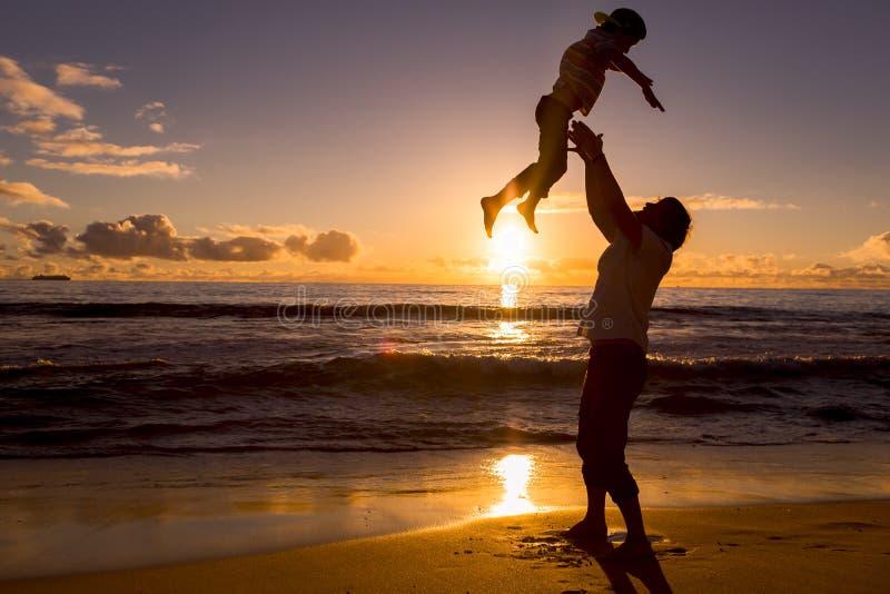 Ο πατέρας και ο γιος έχουν το μεγάλο χρόνο στην παραλία στοκ εικόνες