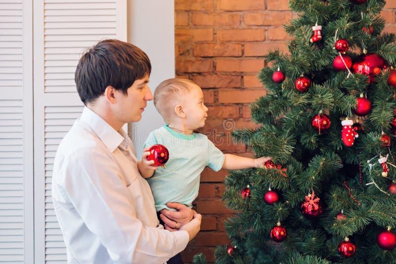 Ο πατέρας και ο γιος διακοσμούν το χριστουγεννιάτικο δέντρο στοκ φωτογραφία