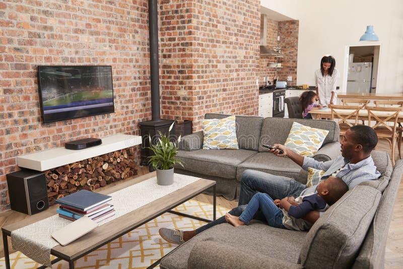 Ο πατέρας και ο γιος κάθονται στον καναπέ στην τηλεόραση προσοχής σαλονιών στοκ φωτογραφίες