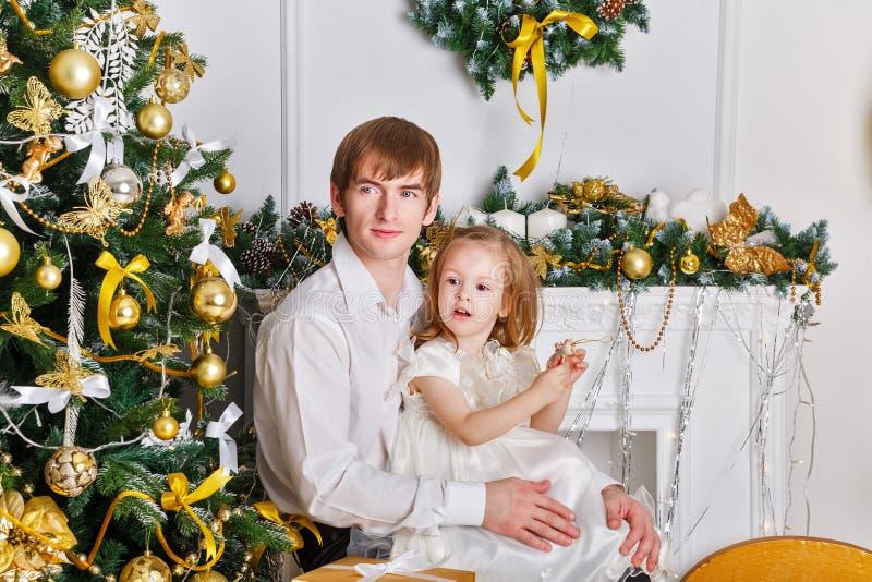 Ο πατέρας κρατά στην κόρη όπλων του Χριστούγεννα στοκ φωτογραφία