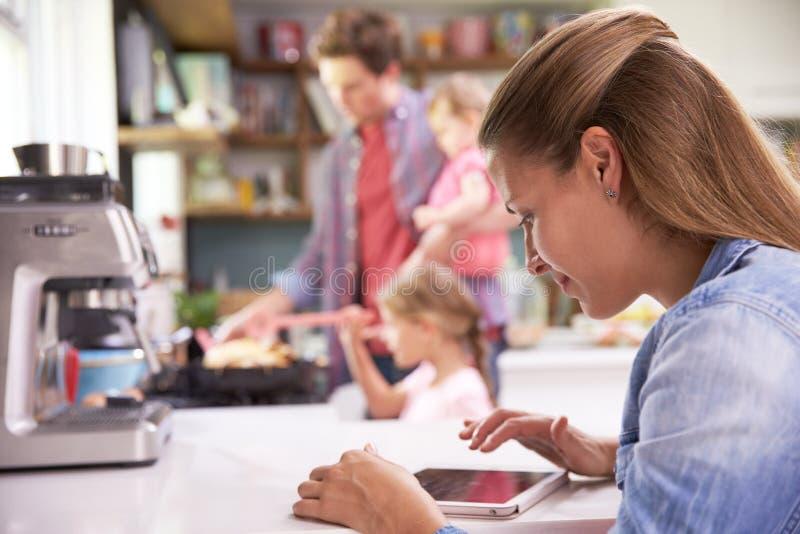 Ο πατέρας μαγειρεύει το οικογενειακό γεύμα ενώ η μητέρα χρησιμοποιεί την ψηφιακή ταμπλέτα στοκ φωτογραφίες με δικαίωμα ελεύθερης χρήσης