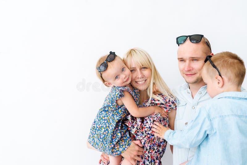 Ο πατέρας, μητέρα και δύο μικρά παιδιά στέκονται μαζί στο άσπρο υπόβαθρο στοκ εικόνες