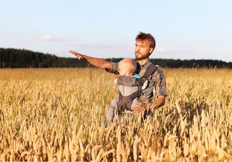 Ο πατέρας παρουσιάζει στο γιο του έναν τομέα του κριθαριού στοκ φωτογραφία με δικαίωμα ελεύθερης χρήσης