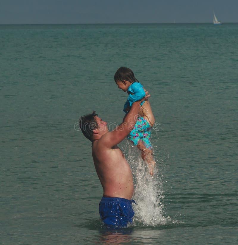 Ο πατέρας ρίχνει την κόρη του νερού στοκ εικόνες