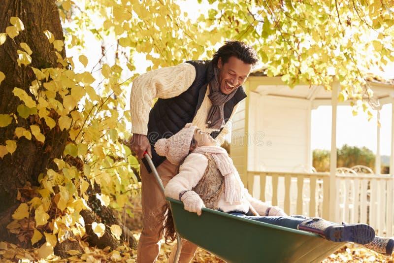 Ο πατέρας στον κήπο φθινοπώρου δίνει το γύρο κορών Wheelbarrow στοκ εικόνες