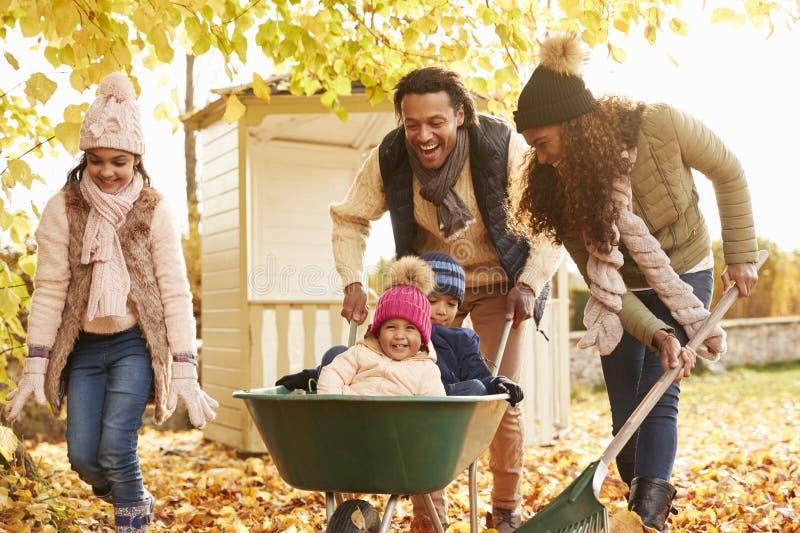 Ο πατέρας στον κήπο φθινοπώρου δίνει το γύρο παιδιών Wheelbarrow στοκ εικόνα με δικαίωμα ελεύθερης χρήσης