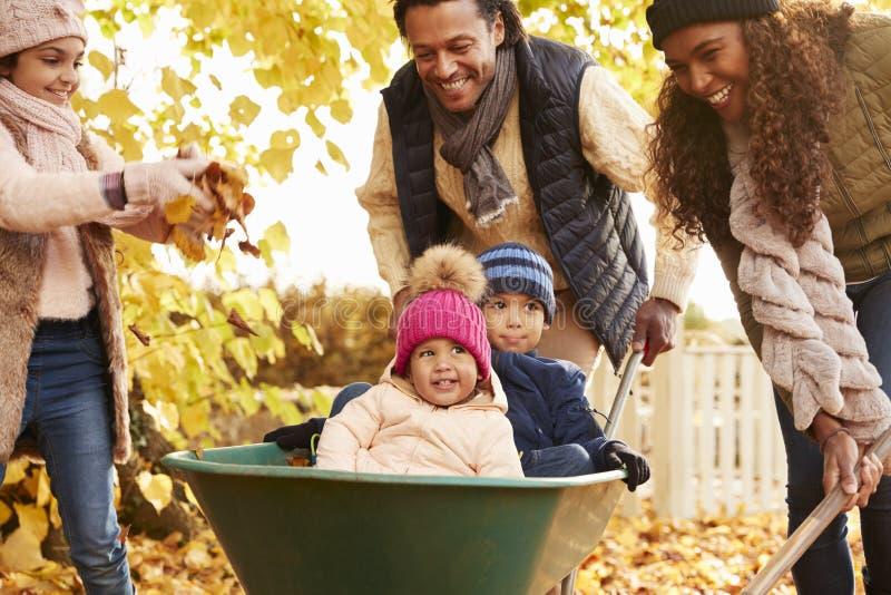Ο πατέρας στον κήπο φθινοπώρου δίνει το γύρο παιδιών Wheelbarrow στοκ εικόνες με δικαίωμα ελεύθερης χρήσης