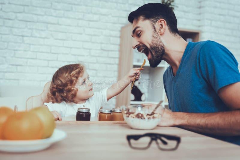Ο πατέρας ταΐζει στους γιους του ένα πρόγευμα στοκ εικόνες