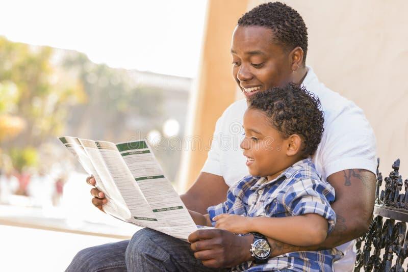 ο πατέρας φυλλάδιων ανάμιξε το γιο ανάγνωσης φυλών πάρκων στοκ εικόνα με δικαίωμα ελεύθερης χρήσης