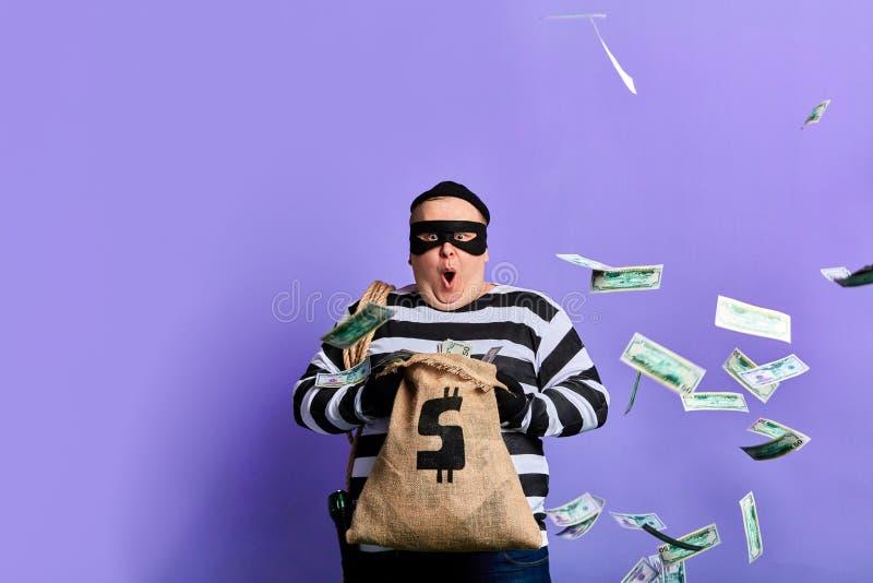 Ο παχουλός κλέφτης είναι έκπληκτος με πολλά χρήματα στο σάκο στοκ φωτογραφία με δικαίωμα ελεύθερης χρήσης