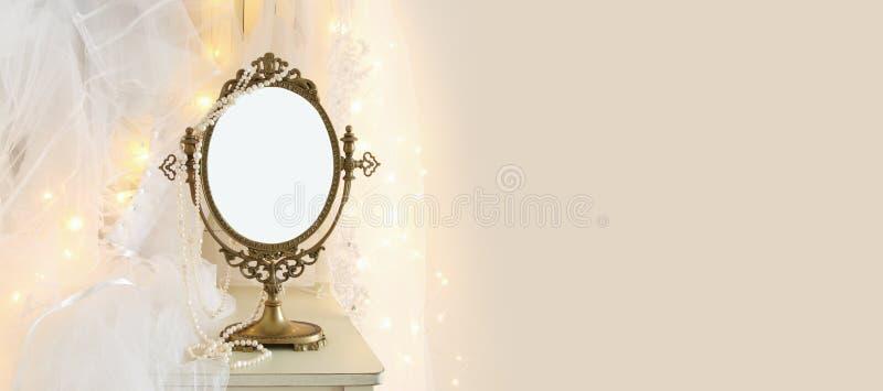 Ο παλαιός εκλεκτής ποιότητας ωοειδής καθρέφτης και ο όμορφος άσπρος γάμος ντύνουν και πέπλο στην καρέκλα με τα χρυσά φω'τα γιρλαν στοκ εικόνα