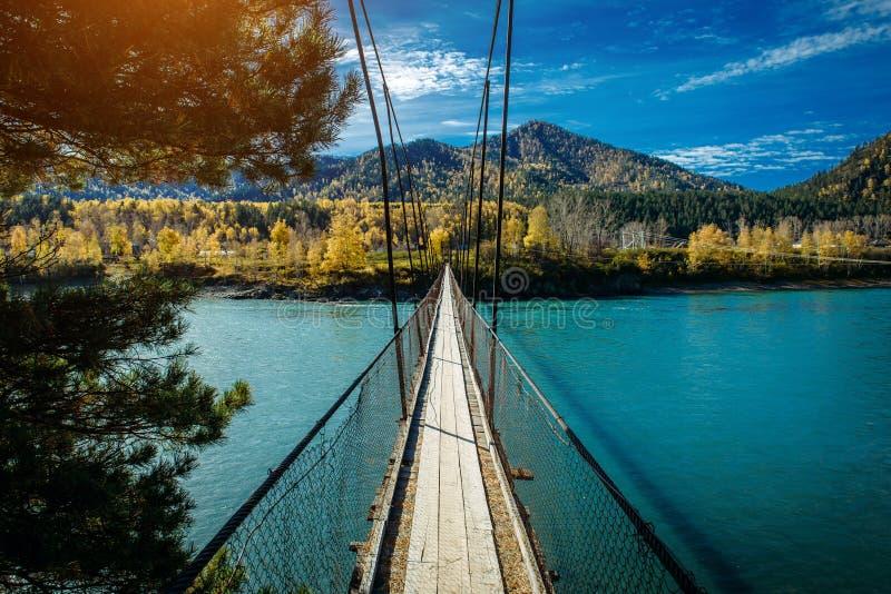 Ο πεζός ανέστειλε την ξύλινη γέφυρα πέρα από τον ποταμό βουνών Μακριά γέφυρα πέρα από τον ποταμό στο κλίμα των βουνών που καλύπτο στοκ φωτογραφία με δικαίωμα ελεύθερης χρήσης