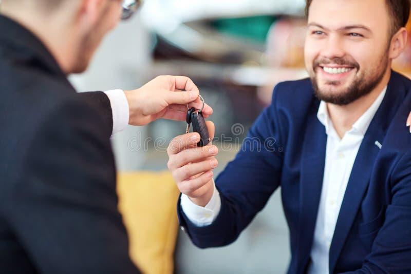 Ο πελάτης παίρνει τα κλειδιά στο αυτοκίνητο από τον πωλητή των αυτοκινήτων στοκ εικόνες