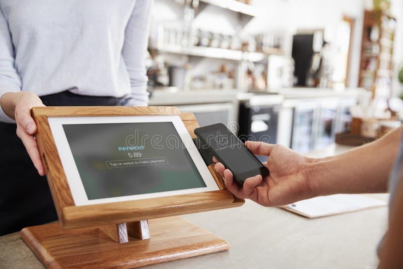 Ο πελάτης που κάνει την πληρωμή από το smartphone στον καφέ, κλείνει επάνω στοκ φωτογραφίες με δικαίωμα ελεύθερης χρήσης