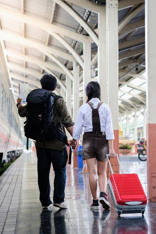 Ο περίπατος χεριών λαβής γυναικών και ανδρών στο σταθμό τρένου πηγαίνει BA έλξης ταξιδιού στοκ εικόνες