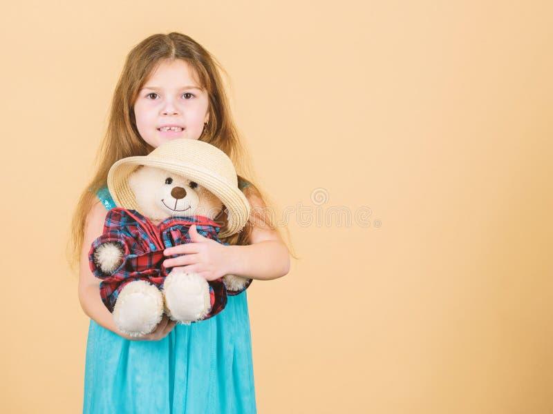 Ο πιό χαριτωμένος πάντα Το μικρό κορίτσι παιδιών αγκαλιάζει προσεκτικά το μαλακό παιχνίδι teddy αντέχει το μπεζ υπόβαθρο Τρυφερές στοκ εικόνα με δικαίωμα ελεύθερης χρήσης