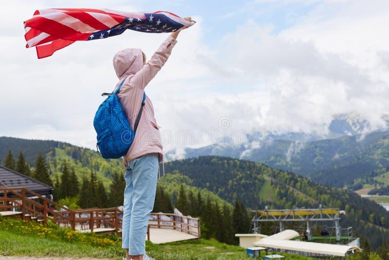 Ο πλήρης πυροβολισμός σχεδιαγράμματος μήκους της όμορφης νέας γυναίκας με τη αμερικανική σημαία που κρατήθηκε σε την το χέρι που  στοκ φωτογραφία