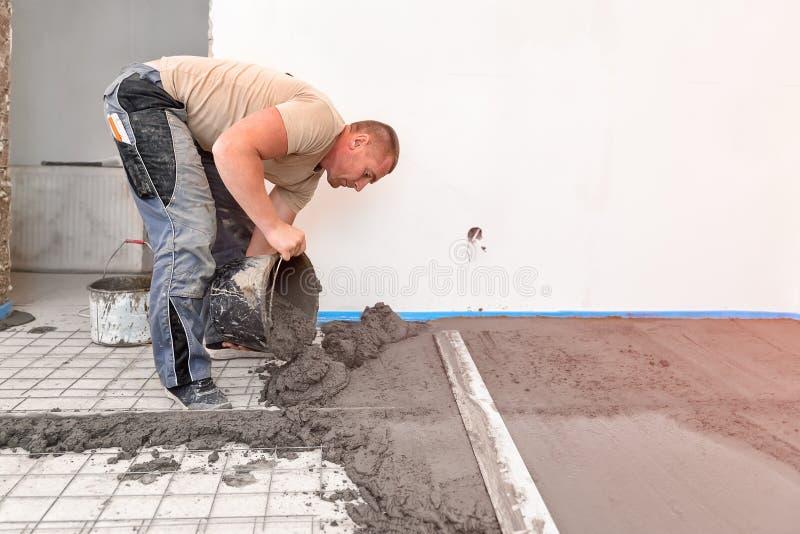 Ο πλινθοκτίστης ευθυγραμμίζει το κατεβατό τσιμέντου σε ένα πρόσφατα χτισμένο σπίτι στοκ φωτογραφίες