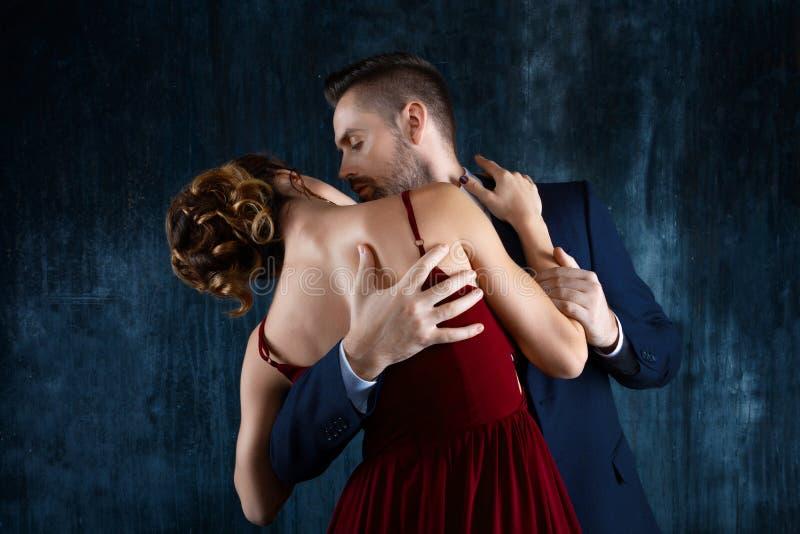 Ο πλούσιος άνθρωπος βάζει στον πειρασμό τη γυναίκα στο κόκκινο φόρεμα βραδιού στοκ φωτογραφίες