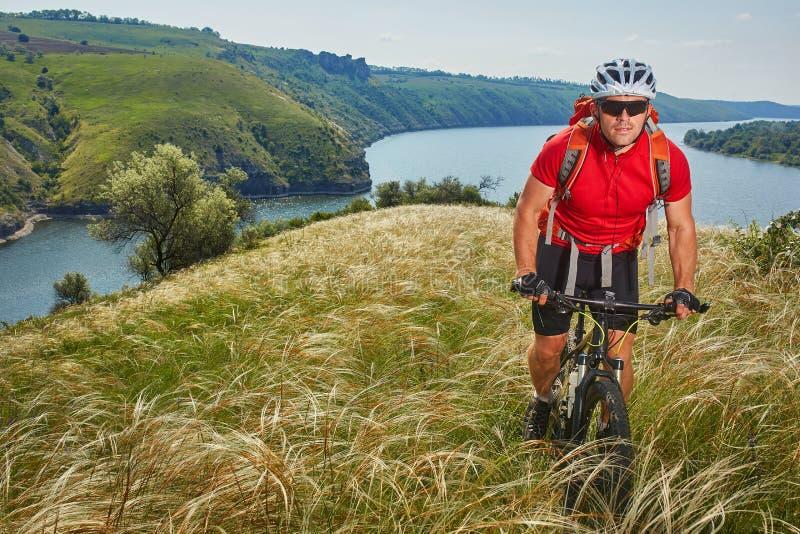 Ο ποδηλάτης έχει την περιπέτεια στο ποδήλατο βουνών του μέσω του πράσινου λιβαδιού ενάντια στον όμορφο ουρανό στοκ εικόνα