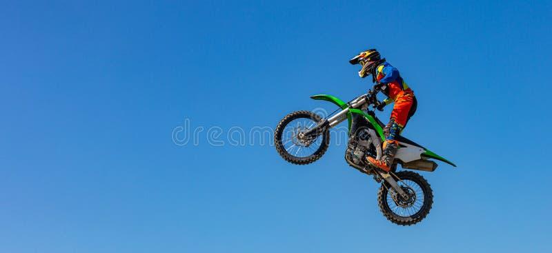 Ο ποδηλάτης κάνει το τέχνασμα και πηδά στον αέρα Ακραία έννοια, αδρεναλίνη r Υπόβαθρο ουρανού στοκ εικόνες