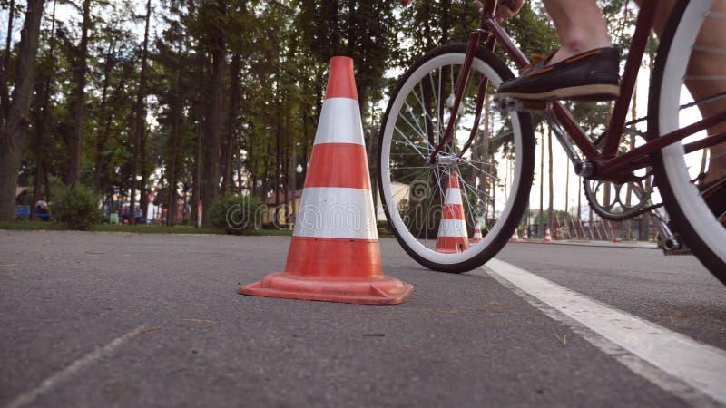 Ο ποδηλάτης πηγαίνει γύρω από τους κώνους κυκλοφορίας Νέο όμορφο άτομο που οδηγά ένα εκλεκτής ποιότητας ποδήλατο Φίλαθλη ανακύκλω στοκ φωτογραφία με δικαίωμα ελεύθερης χρήσης