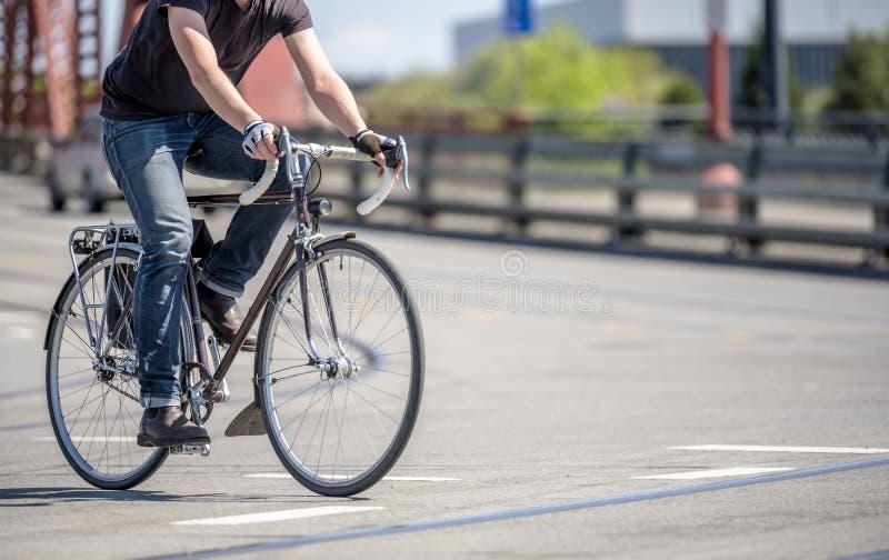 Ο ποδηλάτης στα τζιν προτιμά έναν ενεργό τρόπο ζωής και τις βιασύνες στο ποδήλατο στις γέφυρες πόλεων στοκ εικόνα