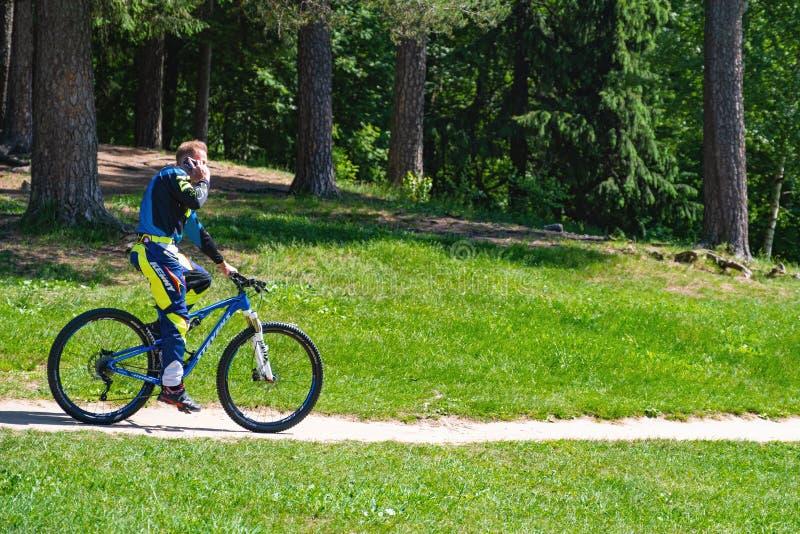 Ο ποδηλάτης στο πάρκο πήρε μια κλήση Σταματημένος για να μιλά στο τηλέφωνο r r 06 12 2019 στοκ εικόνες με δικαίωμα ελεύθερης χρήσης