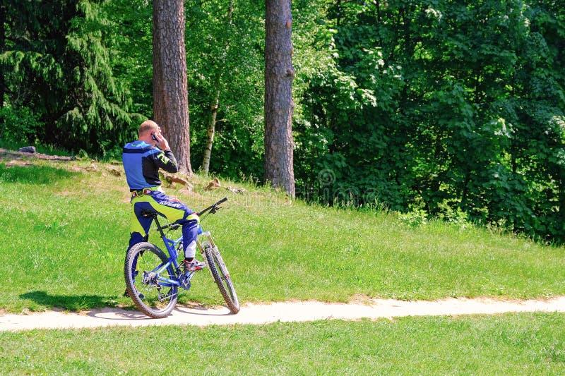 Ο ποδηλάτης στο πάρκο πήρε μια κλήση Σταματημένος για να μιλά στο τηλέφωνο r r 06 12 2019 στοκ εικόνες