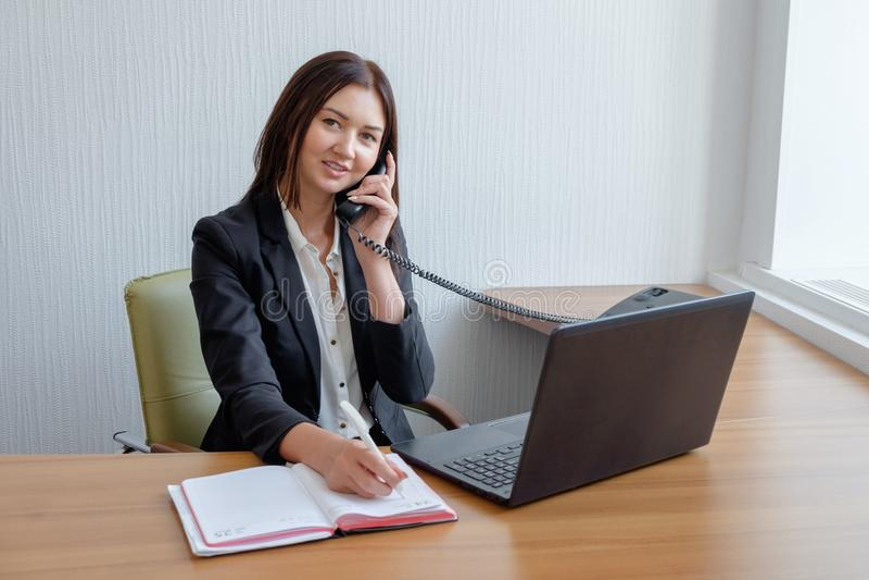 Ο πολυάσχολος γραμματέας απαντά στην κλήση και γράφει το υπόμνημα συγχρόνως στοκ φωτογραφία