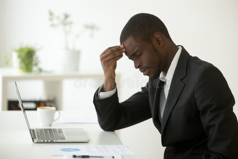 Ο πονοκέφαλος στην έννοια εργασίας, τονισμένος αφρικανικός επιχειρηματίας αισθάνεται το στρεπτόκοκκο στοκ φωτογραφίες