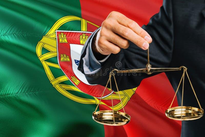 Ο πορτογαλικός δικαστής κρατά τις χρυσές κλίμακες της δικαιοσύνης με το κυματίζοντας υπόβαθρο σημαιών της Πορτογαλίας Θέμα ισότητ στοκ εικόνα