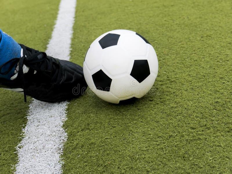 Ο ποδοσφαιριστής κλωτσά τη σφαίρα στον τομέα γηπέδου ποδοσφαίρου στοκ εικόνες