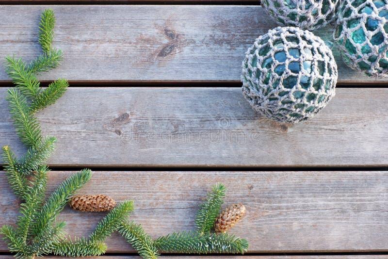 Ο πράσινος κομψός κλάδος βρίσκεται σε ένα ξύλινο υπόβαθρο με τις σφαίρες στο πλέγμα, διάστημα αντιγράφων για το κείμενό σας στοκ φωτογραφία