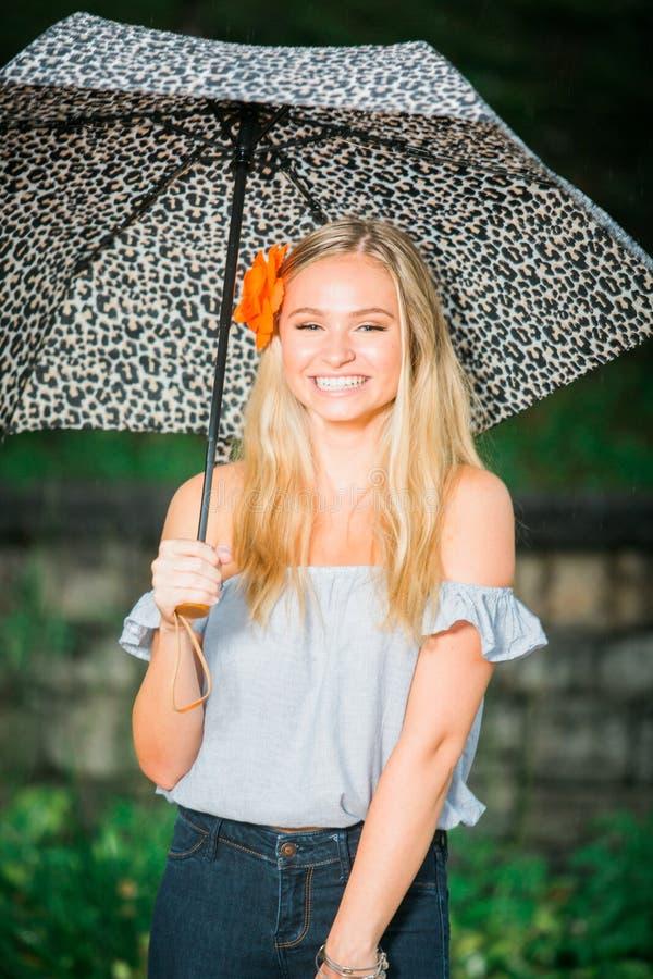 Ο πρεσβύτερος γυμνασίου θέτει με την ομπρέλα για τα πορτρέτα σε έναν βροχερό στοκ εικόνες