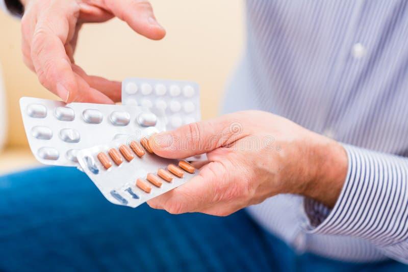 Ο πρεσβύτερος εμποτίζει με τα χάπια στο σπίτι στοκ εικόνες